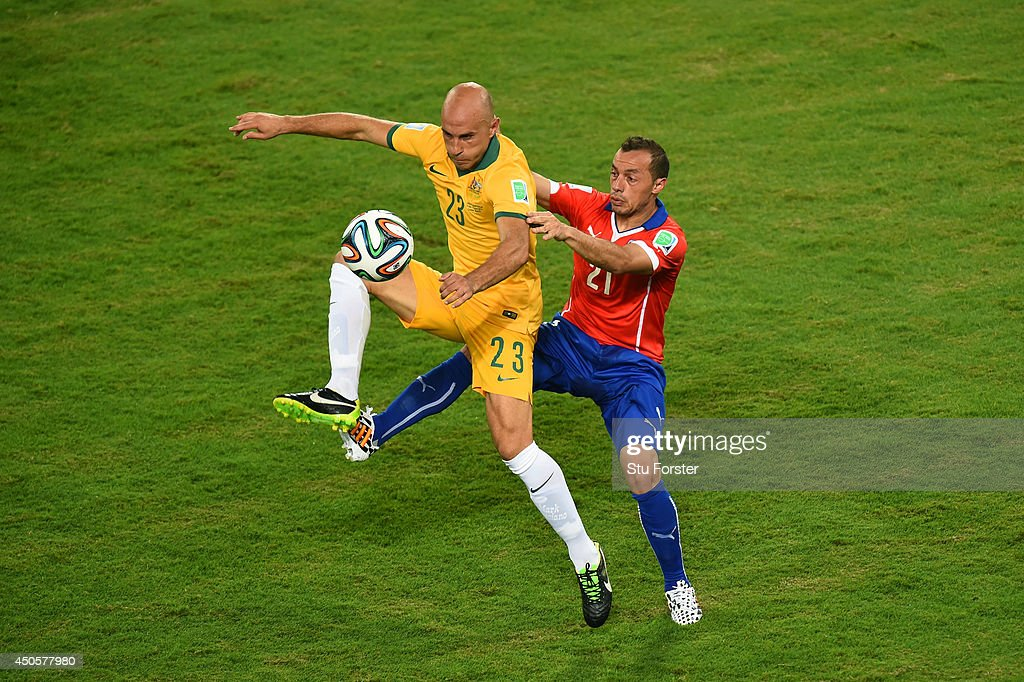Mark Bresciano of Australia is challenged by Marcelo Diaz of Chile during the 2014 FIFA World Cup Brazil Group B match between Chile and Australia at Arena Pantanal on June 13, 2014 in Cuiaba, Brazil.