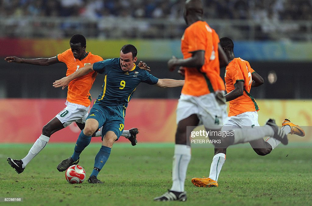 Mark Bridge (C) of Australia fends off defenders from Ivory Coast during their men's first round group A football match at the Beijing 2008 Olympic Games in Tianjin on August 13, 2008. AFP PHOTO/Peter PARKS