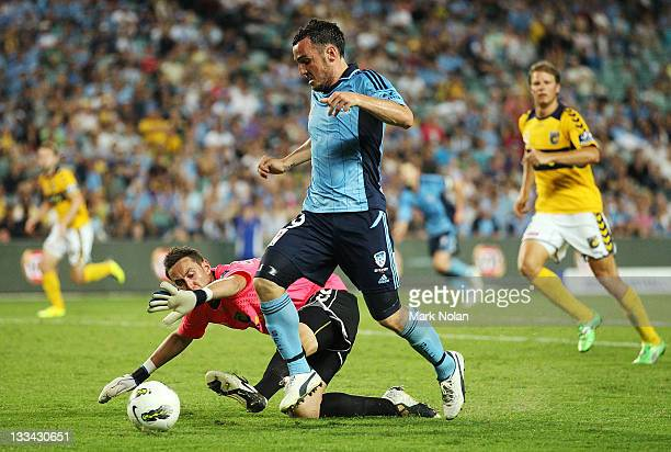 Mark Bridge of Sydney attempts to score as Justin Pasfiled of the Mariners defends his goal during the round seven A-League match between Sydney FC...
