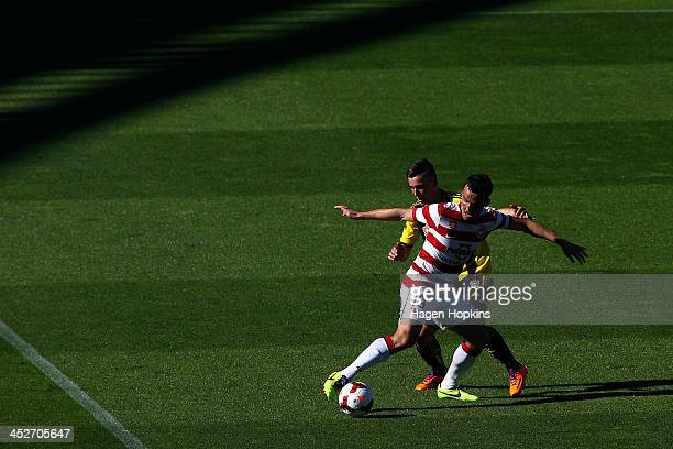 Mark Bridge of the Wanderers holds off the defence of Louis Fenton of the Phoenix during the round eight ALeague match between the Wellington Phoenix...