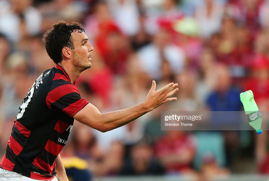 Mark Bridge of the Wanderers removes a bottle off the playing field after being thrown onto the field by a fan during the round 15 A-League match between the Western Sydney Wanderers and the Central Coast Mariners at Parramatta Stadium on January 6, 2013 in Sydney, Australia.