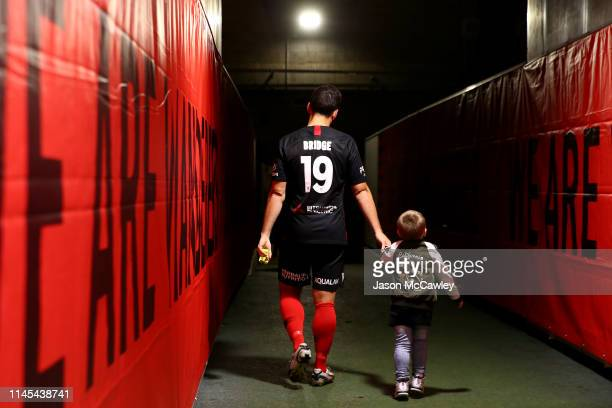 Mark Bridge of the Wanderers walks back to the change rooms with his son after the round 27 A-League match between the Western Sydney Wanderers and...