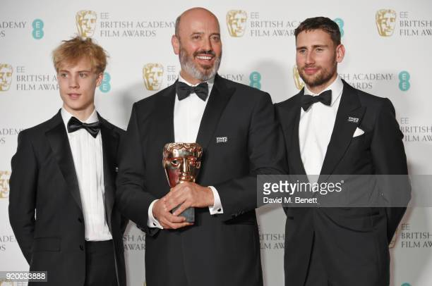 Mark Bridges winner of the Best Costume Design award for 'Phantom Thread' poses with presenters Tom Taylor and Edward Holcroft in the press room...
