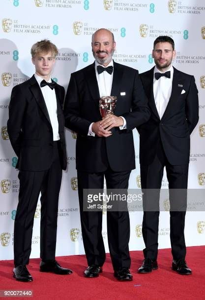 Mark Bridges , winner of the Best Costume Design award for 'Phantom Thread', poses with presenters Tom Taylor and Edward Holcroft in the press room...