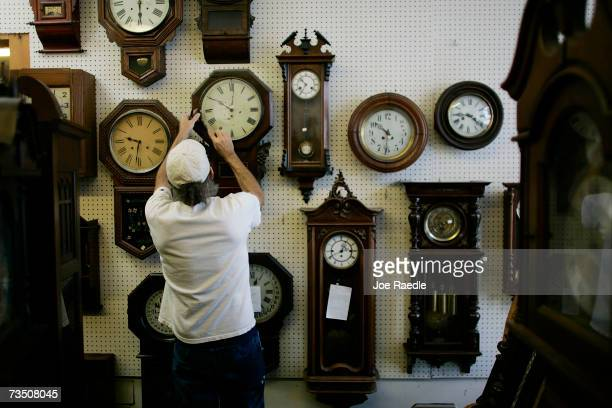 Mark Brown adjusts clocks on the wall at Browns Old Time Clock Shop March 6 2007 in Plantation Florida This year day light savings time happens three...