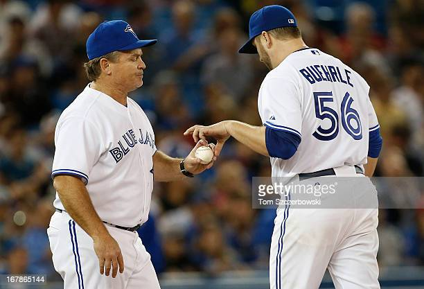 Mark Buehrle of the Toronto Blue Jays is relieved in the seventh inning by manager John Gibbons as he makes a pitching change during MLB game action...