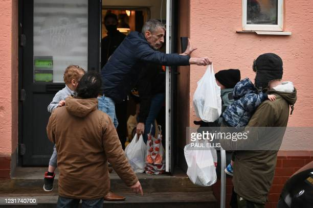Mark Butcher, pastor and lead volunteer at Amazing Graze Soup Kitchen hands out food parcels to people in Blackpool, north west England, on March 9,...