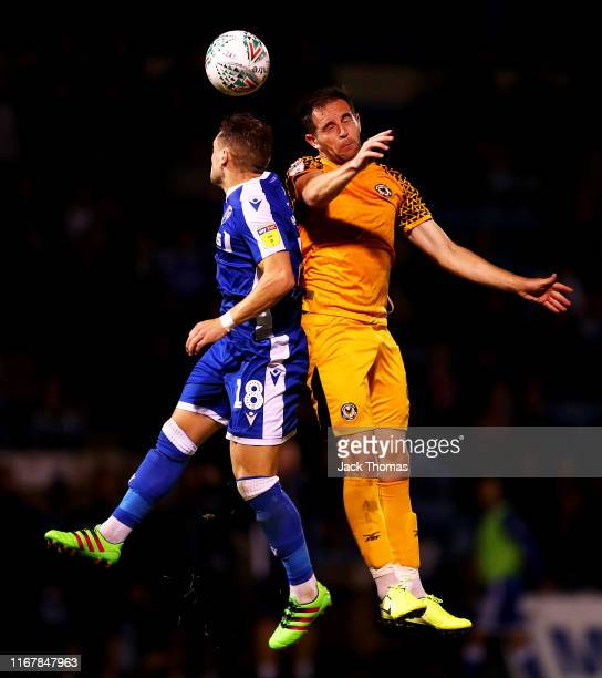 Mark Byrne of Gillingham FC challenges for the ball with Matty Dolan of Newport County during the Carabao Cup First Round match between Gillingham...