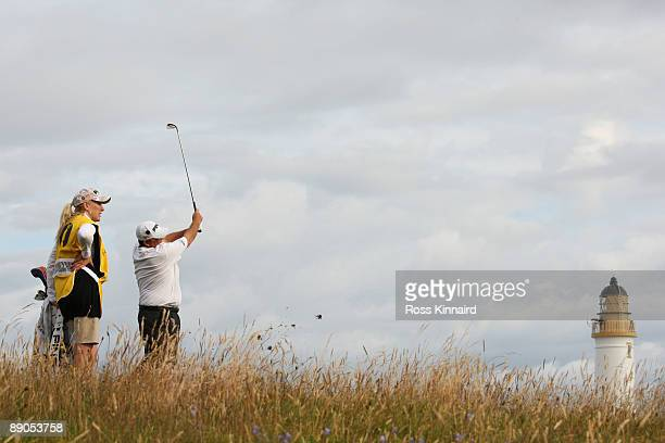 Mark Calcavecchia of USA hits a shot on the ninth hole as his wife/caddy Brenda looks on during round one of the 138th Open Championship on the Ailsa...