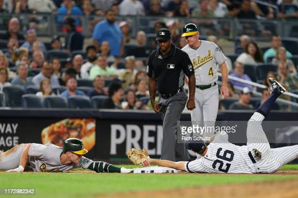 Mark Canha of the Oakland A's slides past third base and dives back safely for an RBI triple before DJ LeMahieu of the New York Yankees can make the...