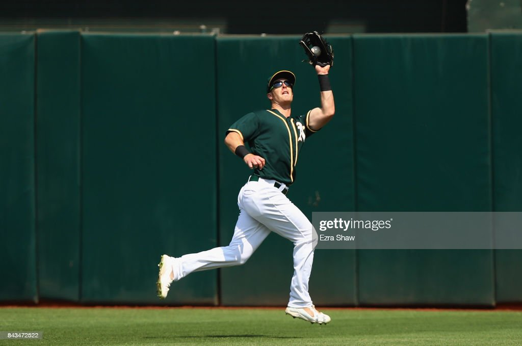 Mark Canha #20 of the Oakland Athletics catches a ball hit by Andrelton Simmons #2 of the Los Angeles Angels in the fourth inning at Oakland Alameda Coliseum on September 6, 2017 in Oakland, California.