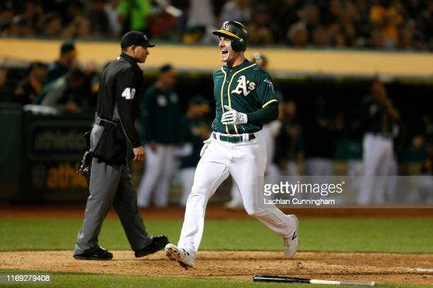 Mark Canha of the Oakland Athletics celebrates as he crosses home plate to score on a tworun single by Stephen Piscotty in the bottom of the sixth...