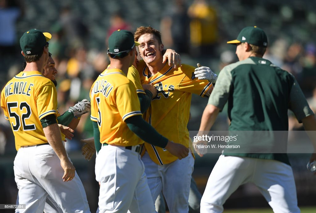 Mark Canha #20 of the Oakland Athletics celebrates with teammates after he hit a walk-off solo home run to defeat the Seattle Mariners 6-5 at Oakland Alameda Coliseum on September 27, 2017 in Oakland, California.