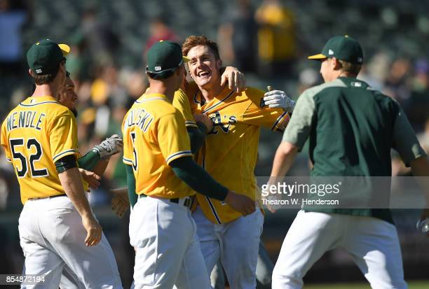 Mark Canha of the Oakland Athletics celebrates with teammates after he hit a walkoff solo home run to defeat the Seattle Mariners 65 at Oakland...