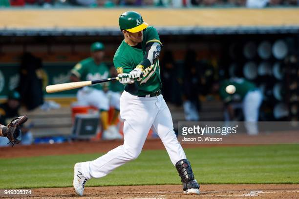 Mark Canha of the Oakland Athletics hits an RBI single against the Boston Red Sox during the first inning at the Oakland Coliseum on April 20 2018 in...