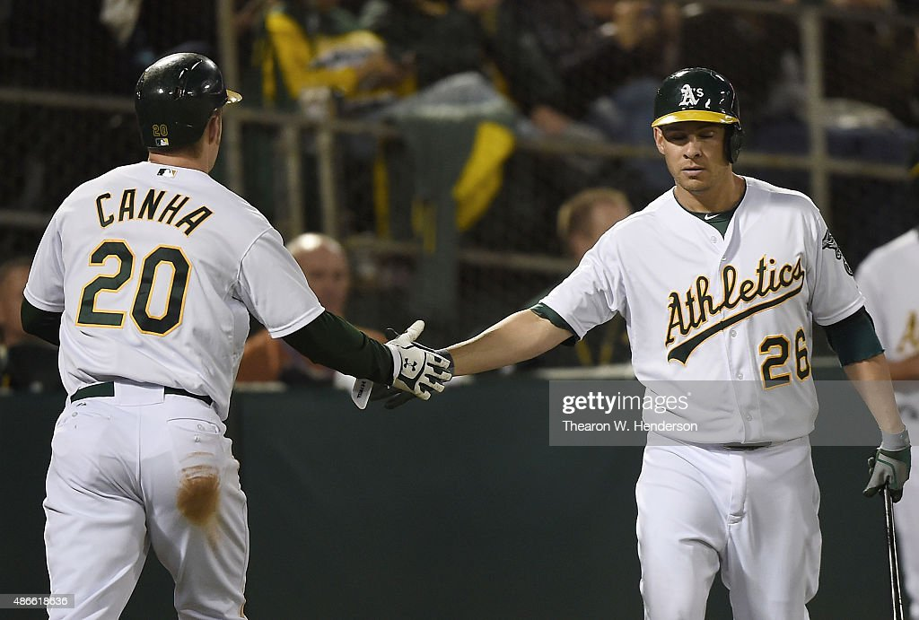 Mark Canha #20 of the Oakland Athletics is congratulated by Danny Valencia #26 after Canha scored against the Seattle Mariners in the bottom of the second inning at O.co Coliseum on September 4, 2015 in Oakland, California.