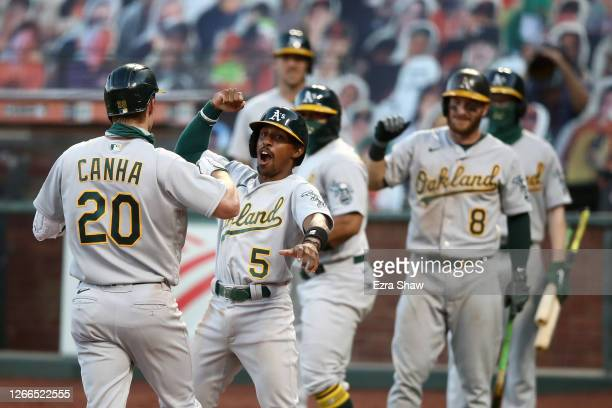 Mark Canha of the Oakland Athletics is congratulated by Tony Kemp after he hit a three-run home run on the ninth inning against the San Francisco...