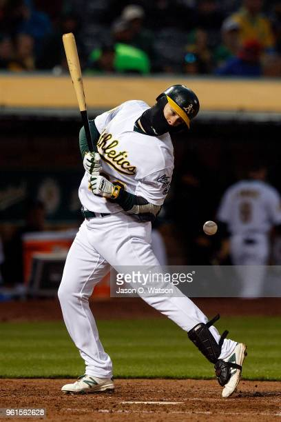 Mark Canha of the Oakland Athletics is hit by a pitch from Mike Leake of the Seattle Mariners during the fifth inning at the Oakland Coliseum on May...