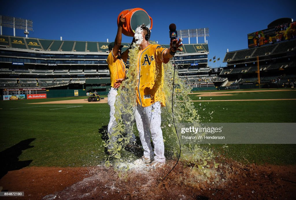 Mark Canha #20 of the Oakland Athletics is showered with Gatorade by teammate Marcus Semien #10 after Canha hit a walk-off solo home run to defeat the Seattle Mariners 6-5 at Oakland Alameda Coliseum on September 27, 2017 in Oakland, California.