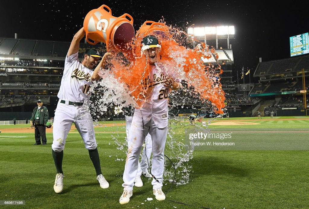 Mark Canha #20 of the Oakland Athletics is soaked with gatorade by Adam Rosales #16 after Canha hit a walk off solo home run to defeat the Boston Red Sox 3-2 in the bottom of the tenth inning at Oakland Alameda Coliseum on May 19, 2017 in Oakland, California.