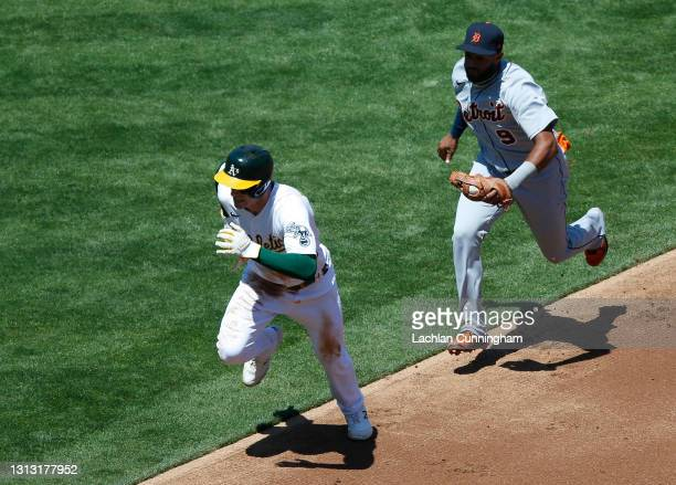 Mark Canha of the Oakland Athletics is tagged out by Willi Castro of the Detroit Tigers after being caught in a run down in the bottom of the first...