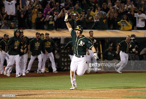 Mark Canha of the Oakland Athletics runs home to score the winning run on a hit by Billy Butler in the 10th inning of their game against the Los...