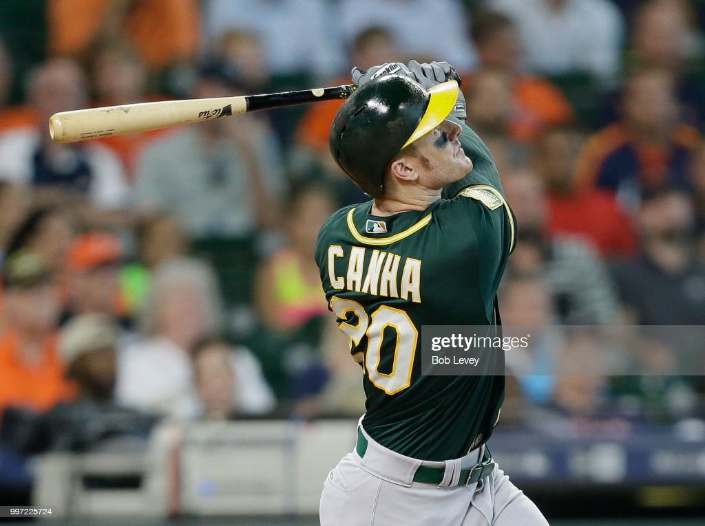 Mark Canha #20 of the Oakland Athletics singles in two runs in the eighth inning against the Houston Astros at Minute Maid Park on July 12, 2018 in Houston, Texas.