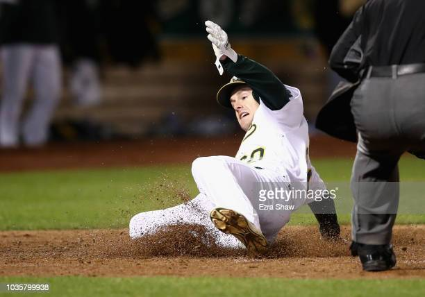Mark Canha of the Oakland Athletics slides home to score on a hit by Jonathan Lucroy in the fourth inning against the Los Angeles Angels at Oakland...