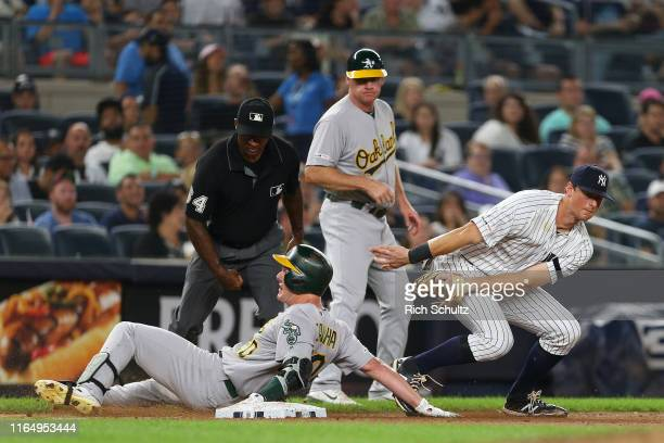 Mark Canha of the Oakland Athletics slides into third base safely with an RBI triple before DJ LeMahieu of the New York Yankees can make the tag...