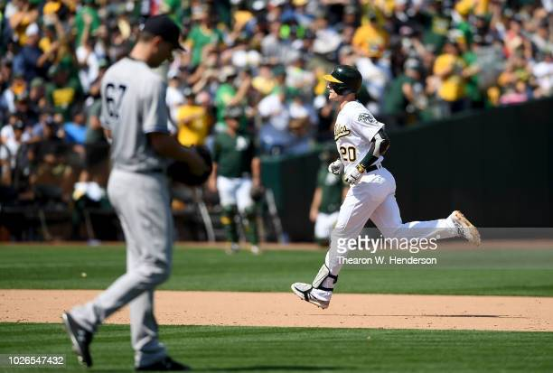 Mark Canha of the Oakland Athletics trots around the bases after hitting a solo home run off of AJ Cole of the New York Yankees in the bottom of the...