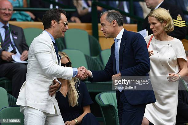 Mark Carney and Jude Law shake hands as Roger Federer of Switzerland plays Milos Raonic of Canada in the Men's Singles Semi Final match on day eleven...