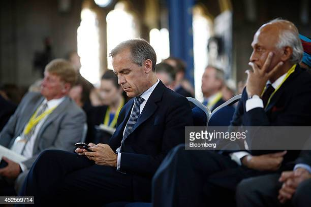 Mark Carney governor of the Bank of England center sits and checks his mobile phone during the Commonwealth Games Business Conference in Glasgow UK...