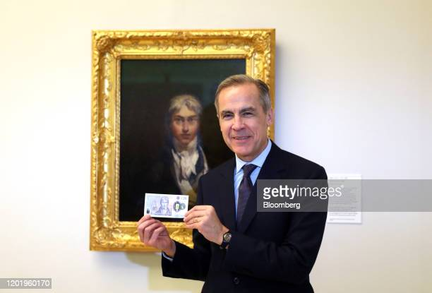Mark Carney governor of the Bank of England holds a new 20pound banknote in front of JMW Turner's self portrait during an event to mark its...