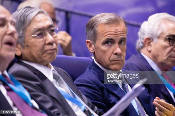 Mark Carney governor of the Bank of England right sits in the audience beside Haruhiko Kuroda governor of the Bank of Japan during the 75th...