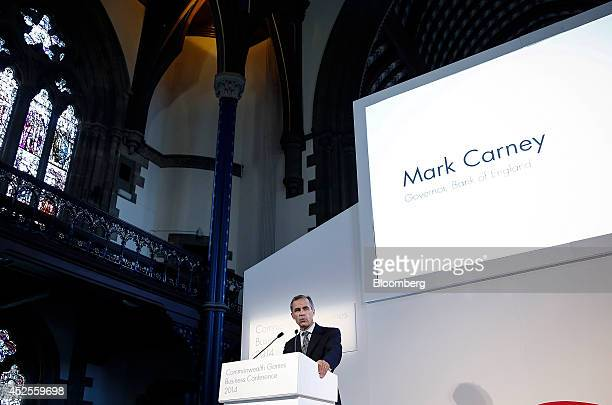 Mark Carney governor of the Bank of England stands at the podium and speaks during the Commonwealth Games Business Conference in Glasgow UK on...