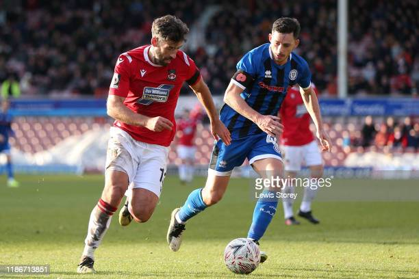 Mark Carrington of Wrexham comes under pressure whilst in possession from Ian Henderson of Rochdale during the FA Cup First Round match between...