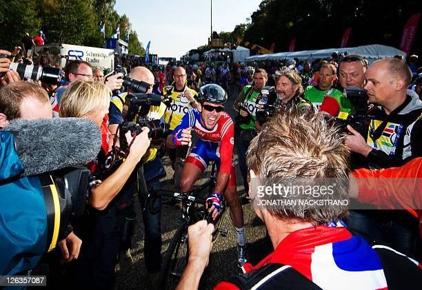 Mark Cavendish of Britain celebrates after crossing the finish line to win the Men Elite Road Race competition on September 25 2011 in Copenhagen The...