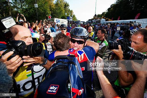 Mark Cavendish of Britain celebrates with a teammate after crossing the finish line to win the Men Elite Road Race competition on September 25 2011...