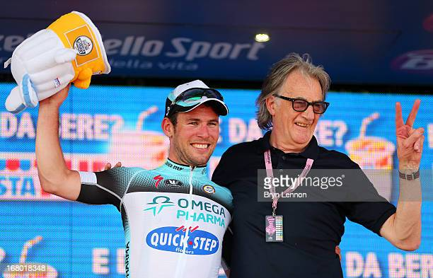 Mark Cavendish of Great Britain and Omega Pharma QuickStep celebrates his stage victory with fashion designer Paul Smith on the podium after stage...