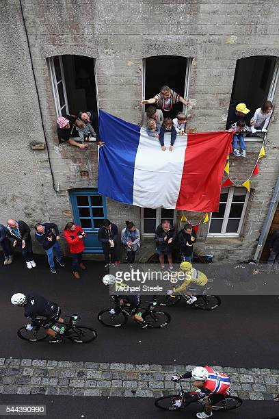 Mark Cavendish of Great Britain and Team Dimension Data wearing the yellow jersey passes through the town of Coutances during stage two of Le Tour de...