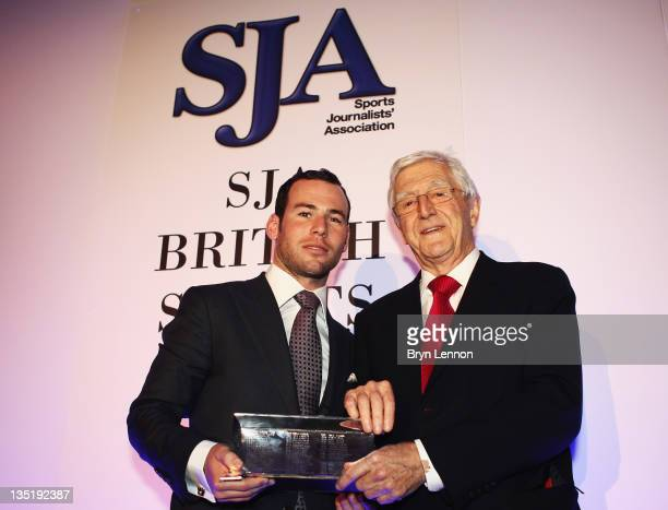 Mark Cavendish of Great Britain receives his Sportsman of the Year award from Sir Michael Parkinson during the SJA 2011 Sports Awards at the Grand...