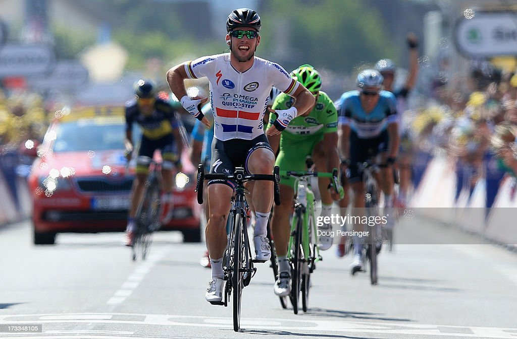 Mark Cavendish of Great Britain riding for Omega Pharma-Quick Step celebrates as he crosses the finish line to win stage thirteen of the 2013 Tour de France, a 173KM road stage from Tours to Saint-Amand-Montrond on July 12, 2013 in Saint-Amand-Montrond, France.