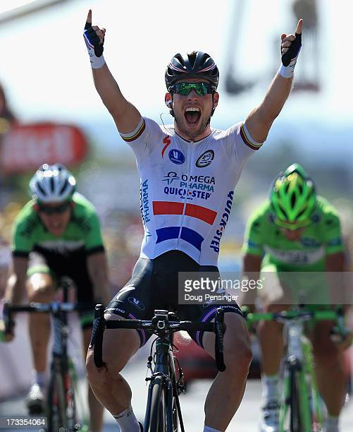 Mark Cavendish of Great Britain riding for Omega PharmaQuick Step celebrates as he crosses the finish line to win stage thirteen of the 2013 Tour de...