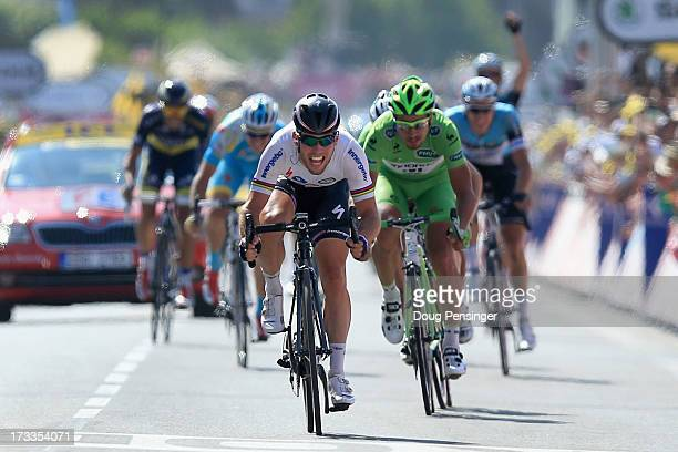 Mark Cavendish of Great Britain riding for Omega Pharma-Quick Step celebrates as he crosses the finish line to win stage thirteen of the 2013 Tour de...