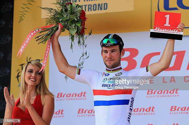 Mark Cavendish of Great Britain riding for Omega Pharma-Quick Step takes the podium for being named the most combative rider of the day after winning...