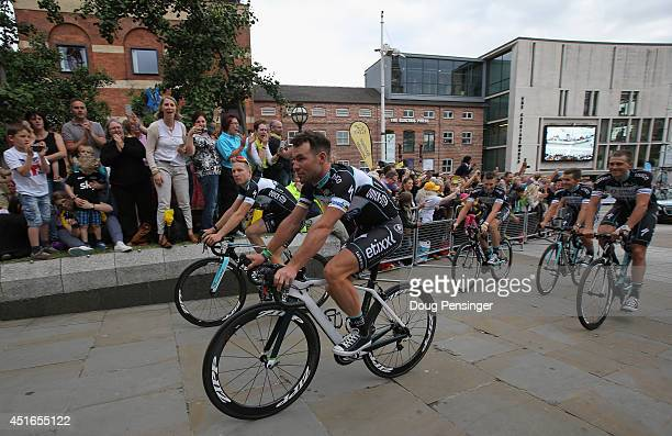 Mark Cavendish of Isle of Man riding for Omega Pharma/QuickStep and his teammates are greeted by supporters as they ride through Millenium Square...