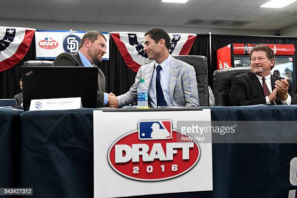 Mark Connor congratulates AJ Preller and Logan White of the San Diego Padres after the selection of the team's first overall draft pick Cal Quantrill...