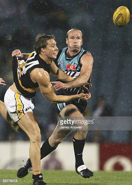 Mark Coughlan of the Tigers and Josh Francou of Port in action during the round 17 AFL match between Port Adelaide Power and the Richmond Tigers at...