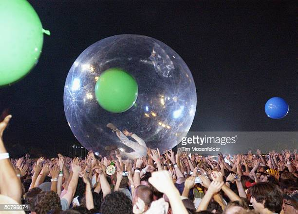 Mark Coyne of The Flaming Lips crowd surfs in an inflatable plastic sphere at the Coachella Music and Arts Festival on May 2 2004 at the Empire Polo...
