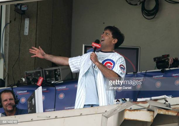 Mark Cuban owner of the Dallas Mavericks sings 'Take Me Out to the Ball Game' during the seventh inning stretch of the game between the Chicago Cubs...